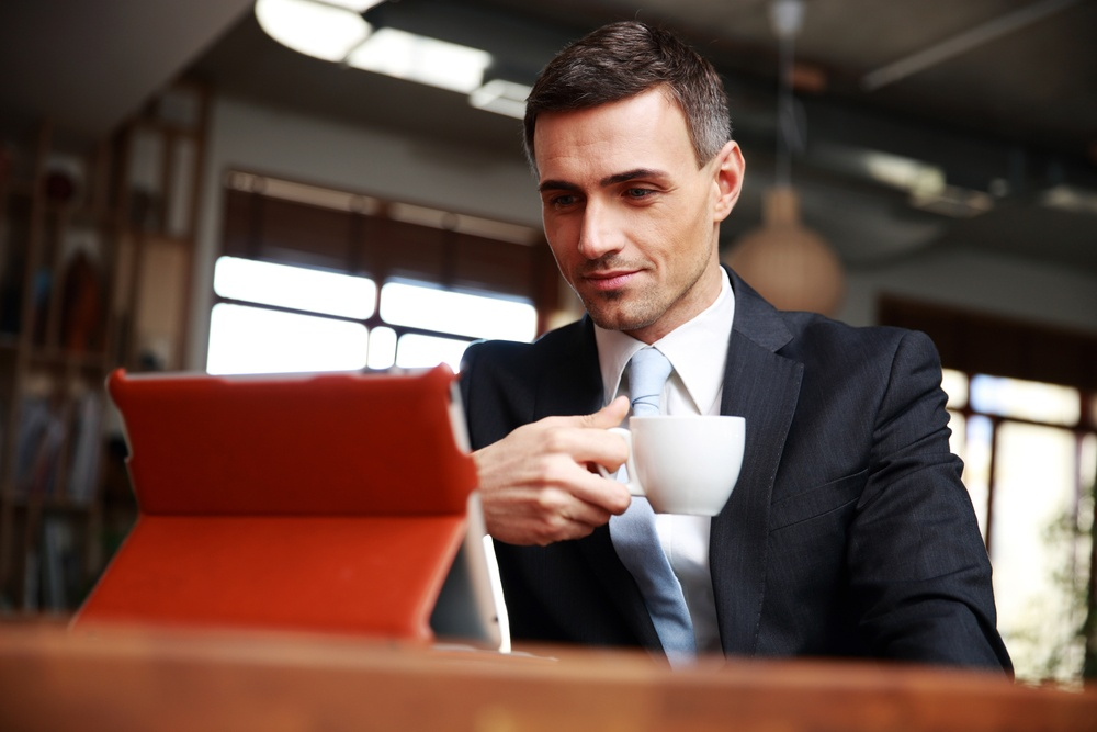 Businessman drinking coffee and reading news in cafe.jpeg
