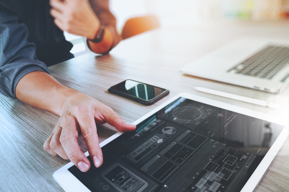 Website designer working digital tablet and computer laptop with smart phone and graphics design diagram on wooden desk as concept-1.jpeg
